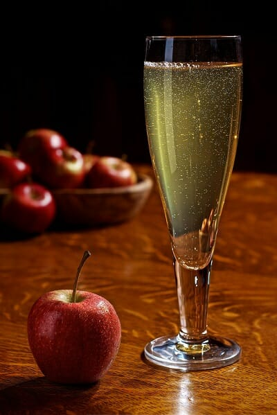 Wine glass of hard cider with apples