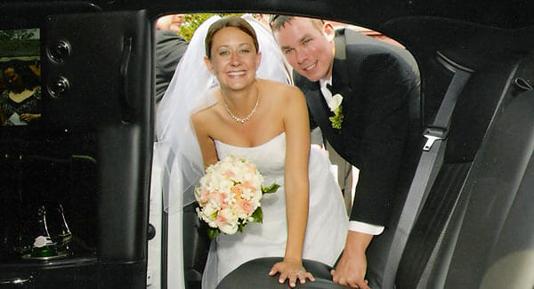 Bride and groom getting into their limo